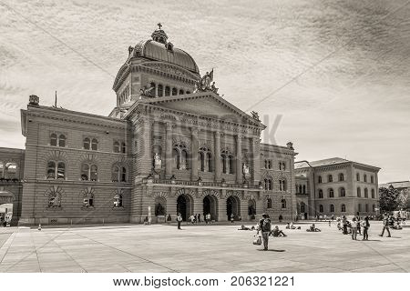 Bern Switzerland - May 26 2016: People are resting on the square in front of the Swiss Parliament Building (Bundesplatz) in Bern Switzerland. Sepia vintage style.