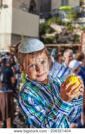 Beautiful Jewish boy with green eyes, in a skullcap, with citrus in his hand. Autumn Jewish holiday Sukkot. The Western Wall of the Temple, Jerusalem, Israel