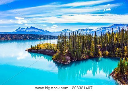 Abraham Lake is in the Rockies of Canada. Turquoise smooth water reflects the sky. Warm sunny day in Indian summer. The concept of ecological and active tourism