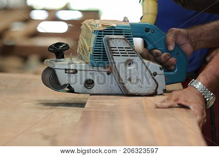 Belt sander on a piece wood with hands of worker. Selective focus and shallow depth of field.