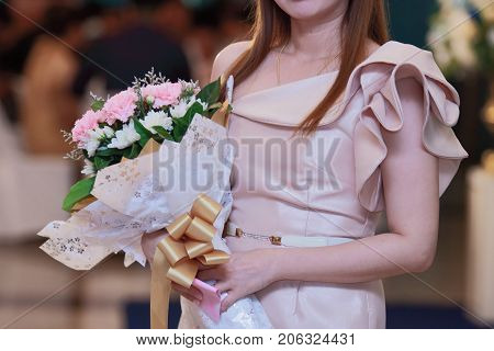 Unidentified attractive woman holding a bouquet of beautiful flowers in her hands. Love and romance concept.
