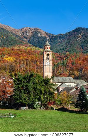Green lawn, parish church belfry and colorful autumnal trees on mountain on background under blue sky in Switzerland.