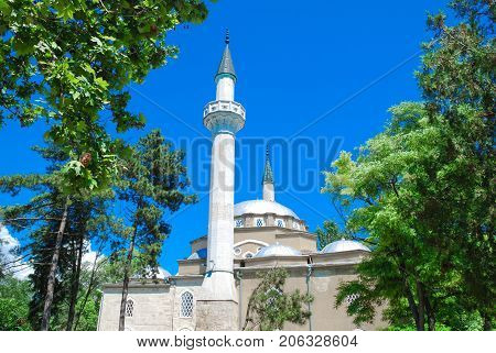 Yevpatoriya Crimea mosque Han-Jami  among green trees, against the sky