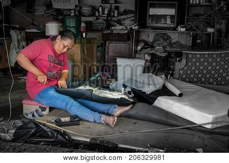 BANGKOK THAILAND - July 1: Underpaid low income migrant worker fixes a motorcycle seat. Due to regular discrimination and lack of labor protection women make up almost 40% of migrant workers in Thailand.