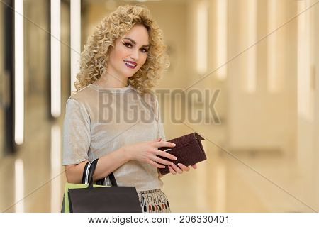 Fashionably Dressed Woman With Shopping Bags In Mall. Young Stylish Girl With Wallet