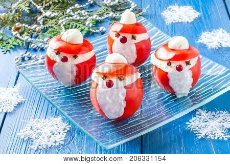 Idea for Christmas party: funny Santa Claus from tomatoes. Tomatoes stuffed with cheese and garlic on plate. Original snack with Christmas and New Year. Christmas decoration. Selective focus