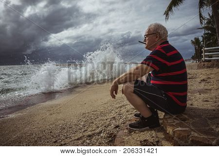 Elderly man in glasses and a striped t-shirt sitting on the beach and looking at the storm smokes a cigar. A wise man in age, the theme of loneliness