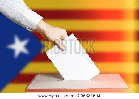 Voter Holds Envelope In Hand Above Vote Ballot. National Catalonia Flag background. Democracy Concept