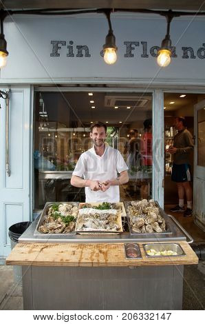 LONDON-UK June 9, 2017:   Man opening fresh oyster at his place in London