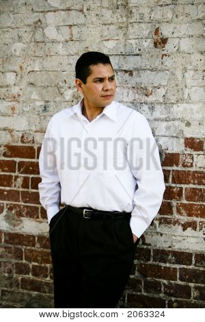Latino background man leaning on a brick wall. poster
