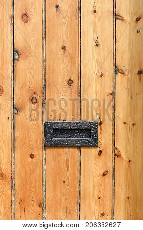 Old rustic cottage striped wooden door with metal letterbox
