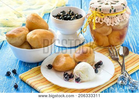 Small rich sponge cake baba typically soaked in rum-flavored syrup. Canned sponge cake rum baba in jar. Is related to brioche and savarin. Served with ice cream rum syrup and blackcurrant poster