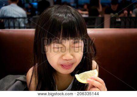 Child's Reaction after Tasting a Slice of Fresh Lemon