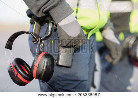 Midsection Of Worker With Ear Protectors Attached To Trouser