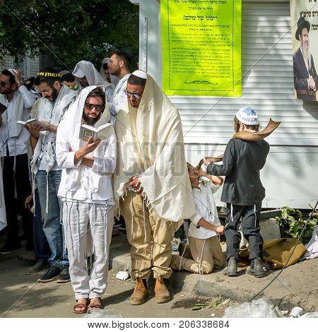 Uman Ukraine - 21 September 2017: Rosh Hashanah Jewish New Year. Mass prayer of pilgrims of Hasidim on the street where Rebbe Nachman the founder of Hasidism is buried. Hasid kids blows Shofar.