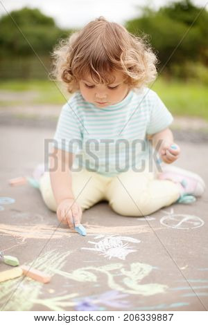 Cute Little Girl Drawing With Color Chalk
