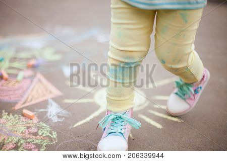 Little cute fun girl enjoy summer days in the park. closeup photo hapiness and childhood concept. chalk drawing on the asphalt