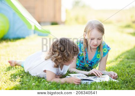 Children stud playing in school yard. learning and doing homework. Schoolgirl reads books to her toddler sister. Sisters relationships.