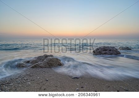 Waves on a beach before night sand rocks orange and blue sky long expositure