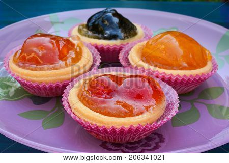 Punnets of dough filled in with various candied fruits served in pink glass plate close up side view poster