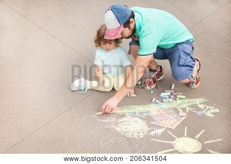 Caring loving father happy family. Single parent single father. Drawing with color chalk. Sunny summer days. Happy childhood. Preschooler leisure time. Kids spending time with parents. Artistic talented kids. Colorful chalk drawing. Children's drawings.