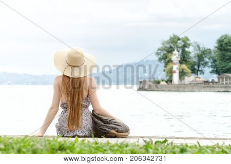 Girl With Long Hair And A Hat Sitting On The Pier With A Backpack. Lighthouse In The Distance