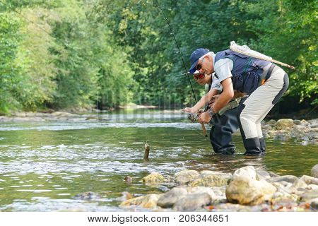 Father and son fly-fishing and catching rainbow trout in river