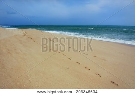 Footprints on sea shore. Beach and tropical sea. Paradise idyllic beach Sri Lanka. Beautiful Sri Lanka landscape. Exotic water landscape with clouds on horizon. Summer holidays. Ocean shore in the evening as nature travel background.