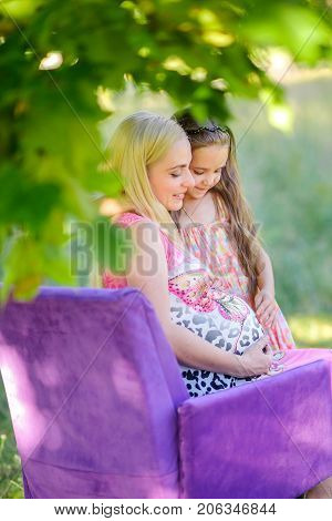 young couple with the senior daughter waiting for the child's birth embraces and kisses in the park against the background of greens the gentle loving relations happy pregnancy