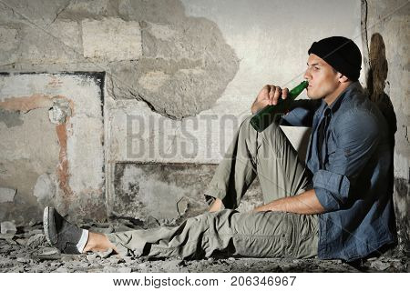 Man sitting and drinking alcohol in abandoned building