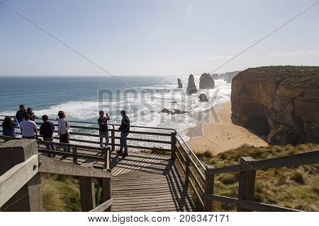Melbourne, Australia: October 8, 2015: Tourists look enjoy the Twelve Apostle Sea Rocks from the viewing boardwalk provided and maintained by the Port Campbell National Park.