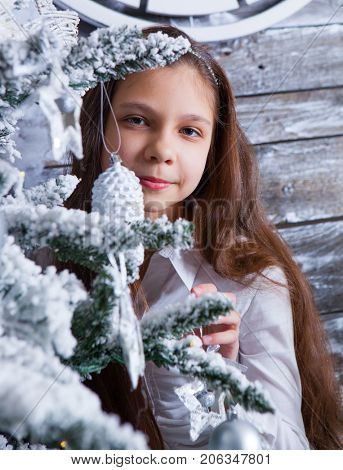 Smiling girl with Christmas decoration and New Year tree