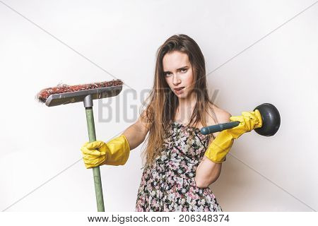 beautiful girl in a dress with a mop in hands is engaged in cleaning