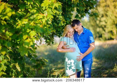 young couple waiting for the child's birth embraces and kisses in the park against the background of greens the gentle loving relations happy pregnancy