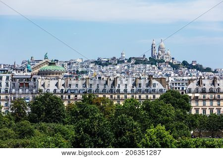 Panorama of Paris with Basilica of the Sacred Heart of Paris (Basilique du Sacre Coeur) on Montmartre hill and Palais Garnier opera house viewed from Orsay Museum. Paris France