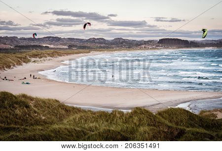 Two kitesurfers in action having fun on cold stormy sunset evening at Brusand Beach, Norway.