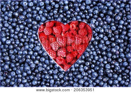 Heart from raspberries on a background of fresh ripe blueberries. Concept of health. Close-up.