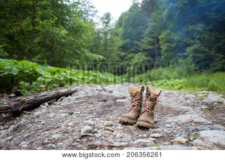 Hiking boots of a tourist lying on a rocky shore of mountain river in the forest. Lifestyle Hiking adventure. Selective focus.