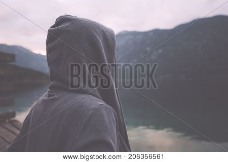 Gloomy nostalgic portrait of sad lonely melancholic adult female with hooded jacket standing on the lake shore in misty overcast morning and thinking in solitude about personal problems retro toned image