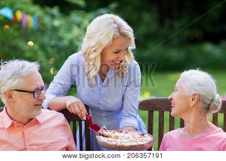 leisure, holidays and people concept - happy family sharing pie at festive dinner or summer garden party
