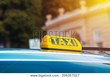 Yellow taxi sign on cab vehicle roof selective focus