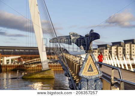 Swansea, UK: February 2017: A woman wearing a red coat crosses the footbridge over the River Tawe walking toward the camera. The National Cycle Network sign gives directions to Pontardawe and Llanelli