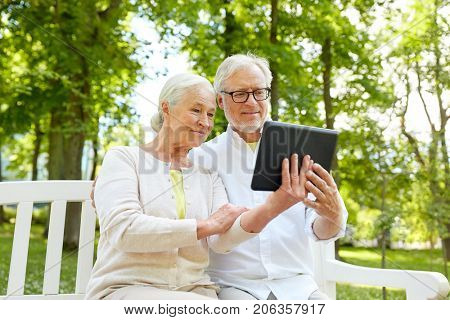 old age, technology and people concept - happy senior couple with tablet pc computer in city park