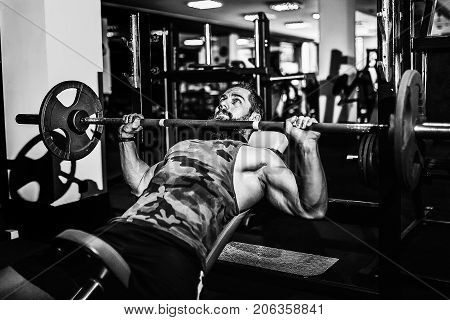 Very Strong bearded man doing bench press workout in gym