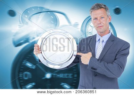 Portrait of businessman pointing at wall clock against graphic image of alarm and wall clocks