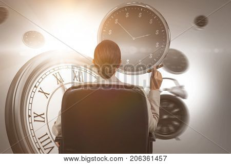 Rear view of female executive holding cigar against computer generated image of clocks
