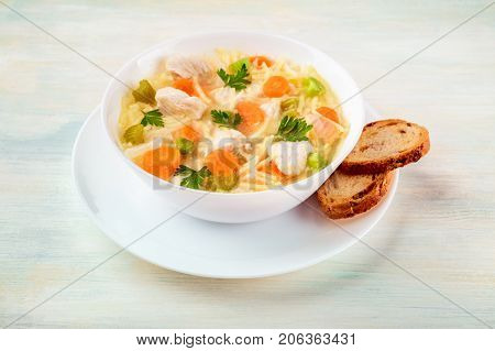 A photo of a plate of chicken, vegetables, and noodles soup, shot on a light texture with slices of bread, selective focus