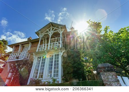Country House With Green Fence In The Region Of Normandy, France On A Sunny Day With Sunbeams In Blu