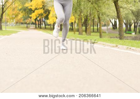 Woman with athletic legs on jog or run on trail in forest in healthy lifestyle concept. Female athlete jogging and training outdoors