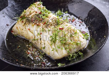 Fried cod fish fillet with spice and cress as close-up in a cast iron pan